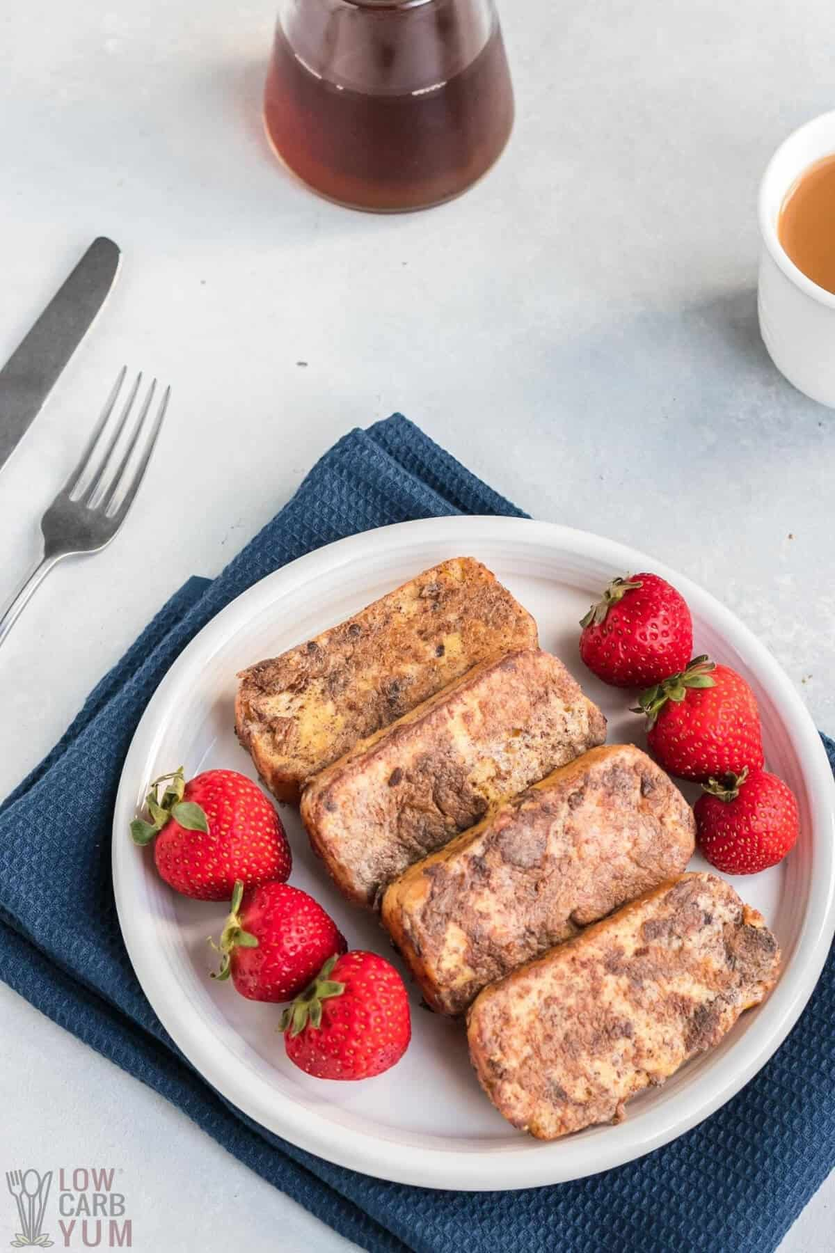 four slices of low-carb french toast on white plate with strawberries