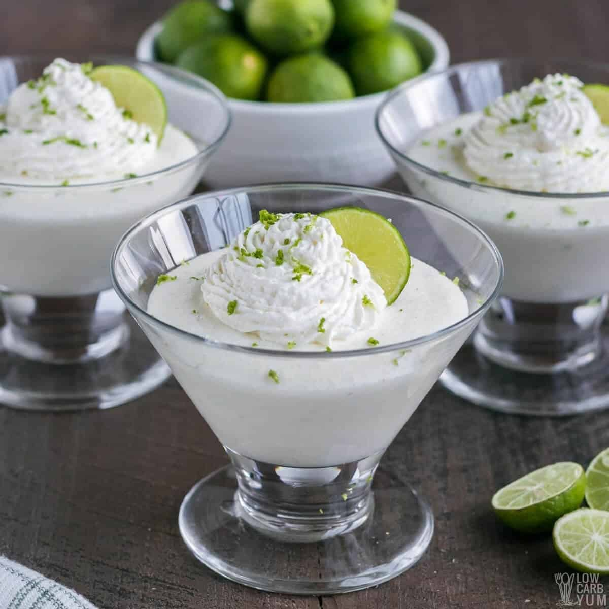 key lime mousse in glass dessert dishes with whipped cream and lime