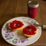 low carb raspberry jam on bagel with spreader and jar of jam