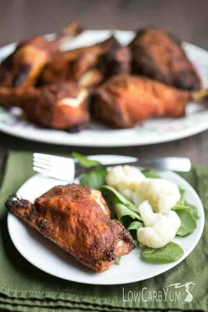 crispy baked chicken legs and thighs on plate and platter