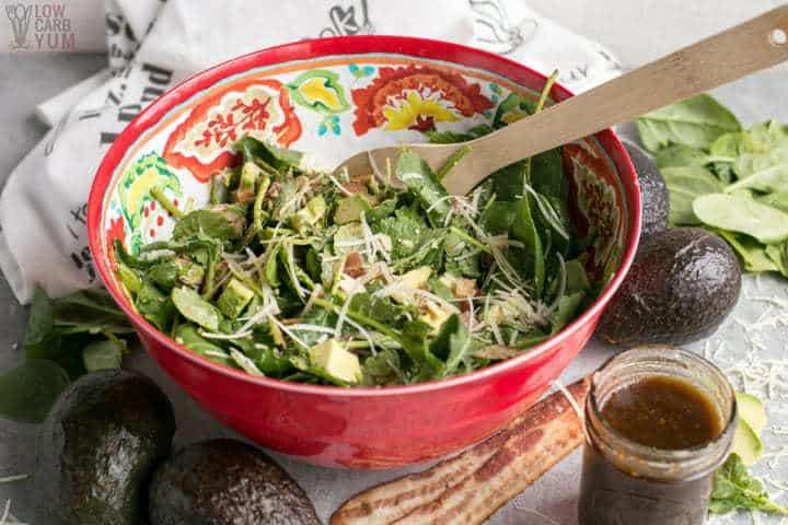 Bowl of baby kale avocado salad with parmesan cheese