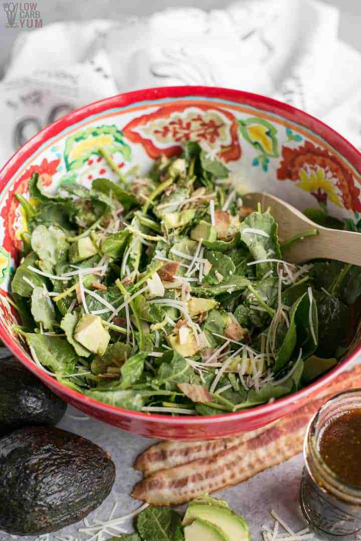 Big bowl of baby kale avocado salad with parmesan cheese