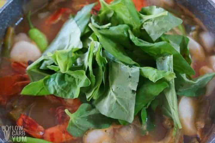 Adding spinach to the Filipino soup