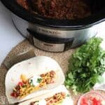 Crock Pot Tacos on plate with taco meat in crock pot