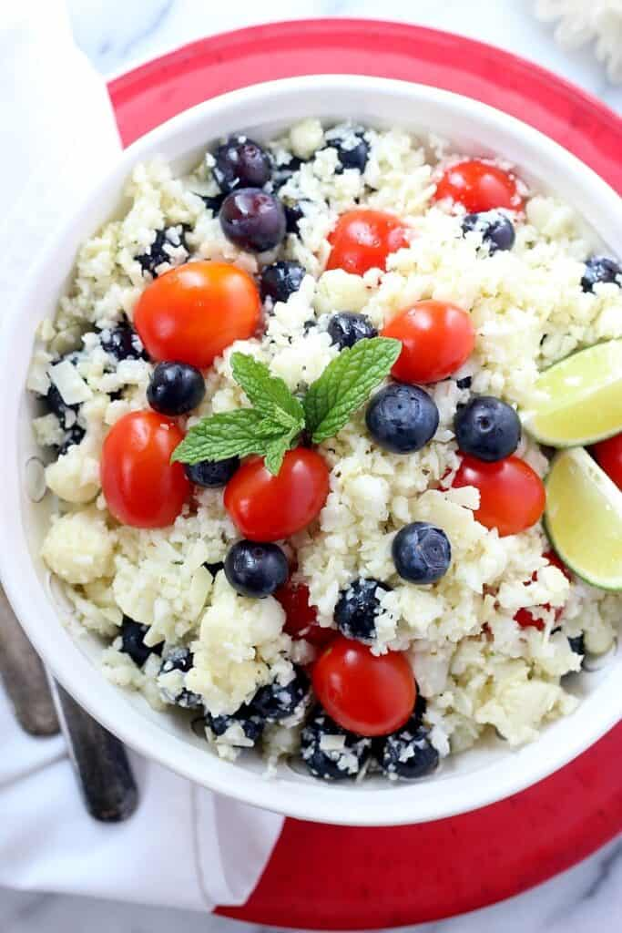 bowl of healthy Parmesan cauliflower rice salad with cherry tomatoes and fresh blueberries