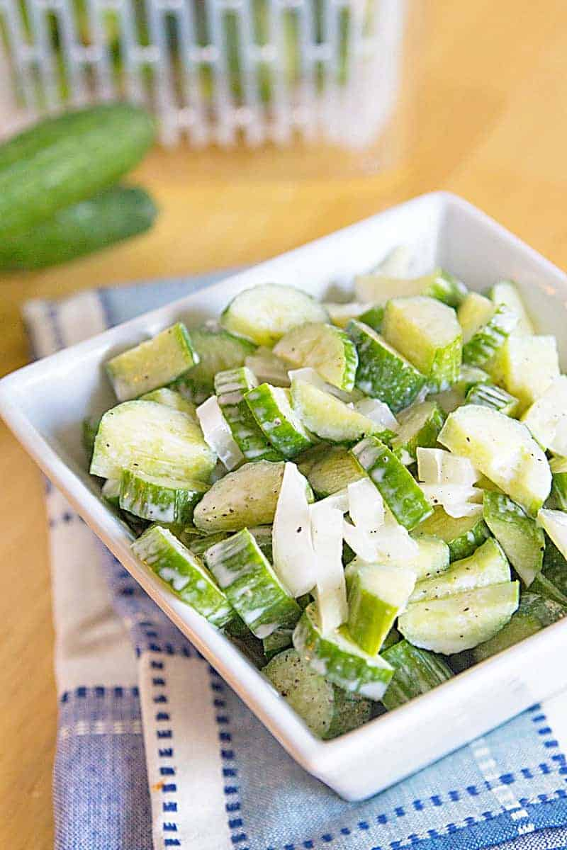 Low Carb Cucumber Salad in square bowl with cucumber in background