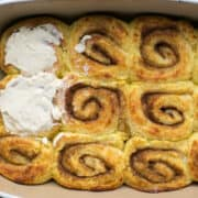 keto cinnamon rolls in pan with cream cheese frosting