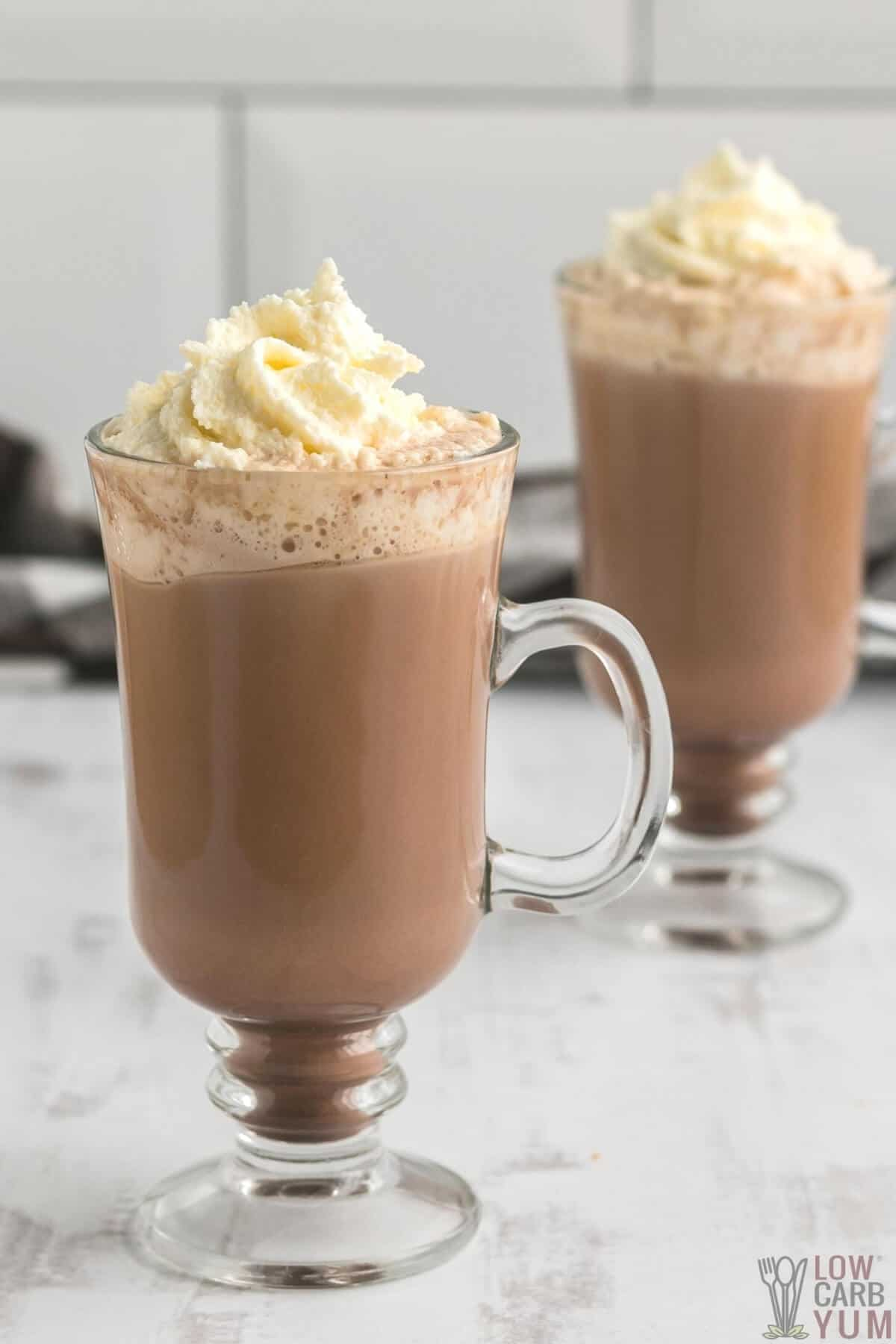 two glass cups of sugar free low carb keto hot chocolate topped with whipped cream