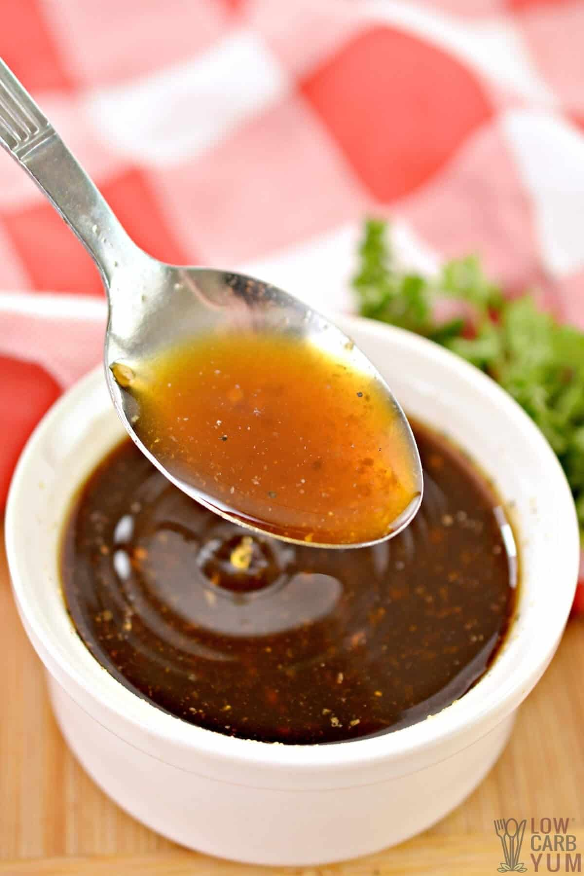 spoon of sauce over cup of whisked ingredients