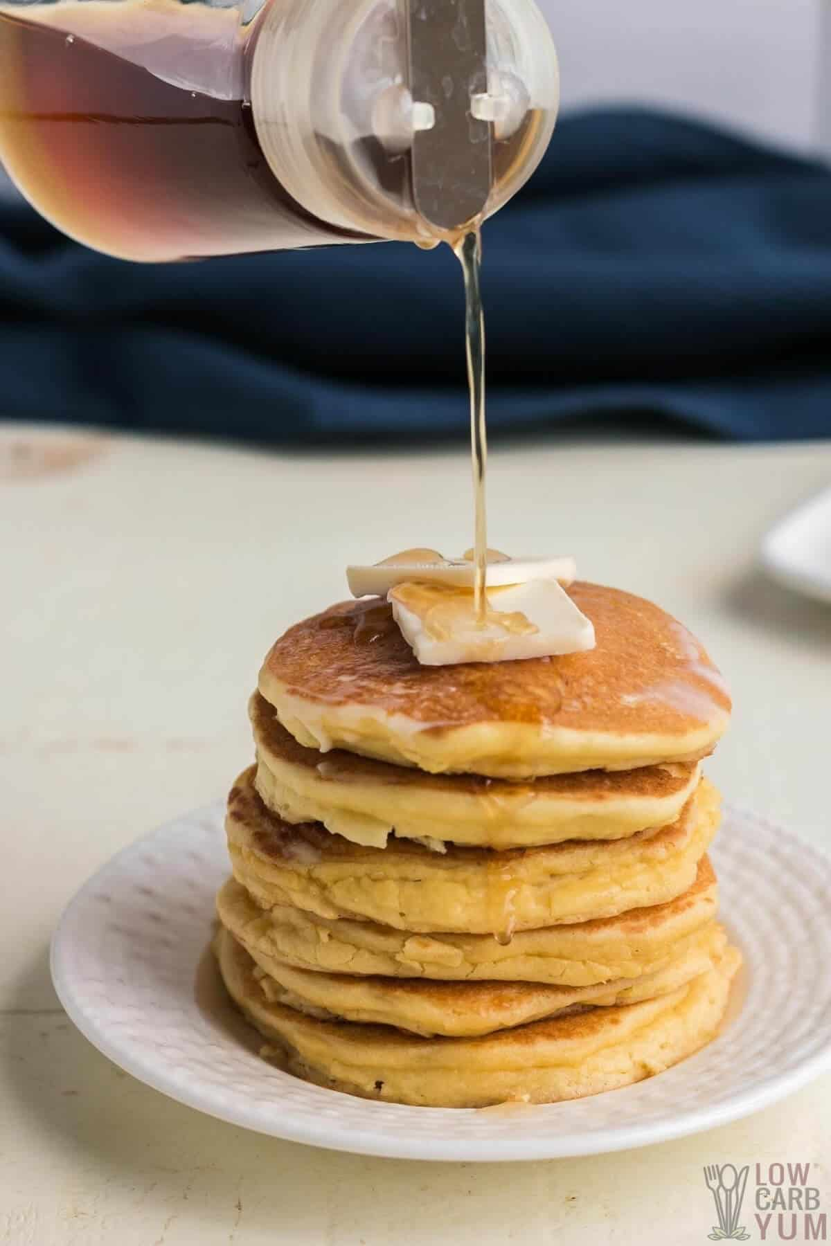pouring syrup on oat fiber pancakes stack