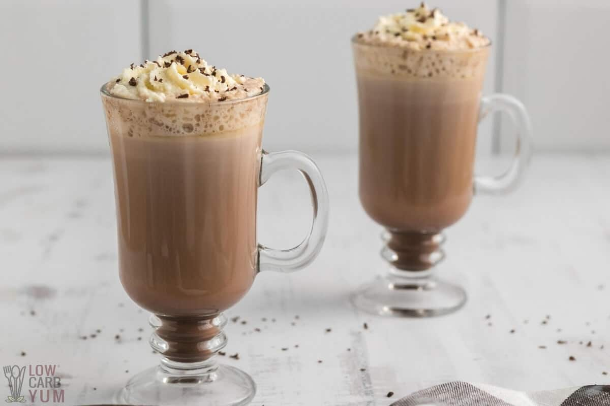 two glasses of sugar free low carb hot chocolate with whipped cream and grated chocolate