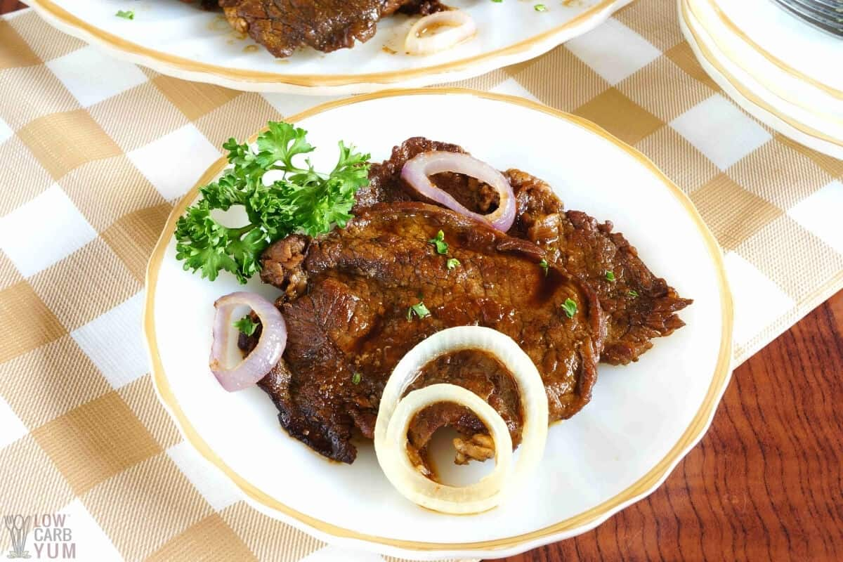 filipino beef steak on white plate with sliced onions