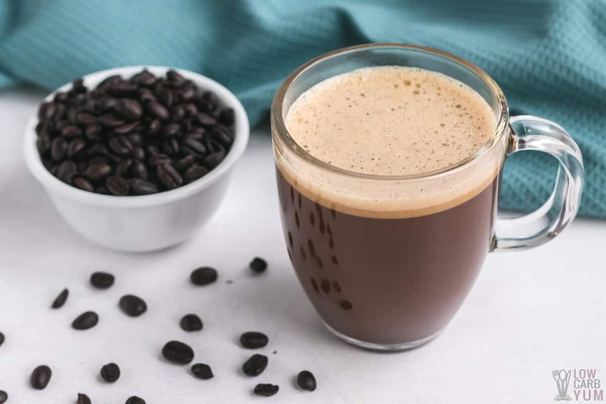 homemade bulletproof coffee in glass cup with coffee beans
