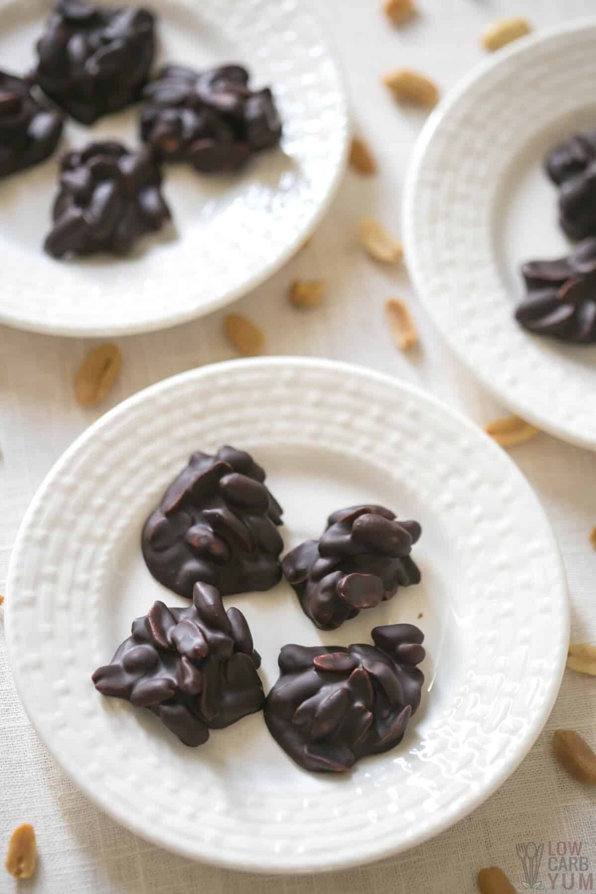 homemade chocolate peanut clusters on white plates
