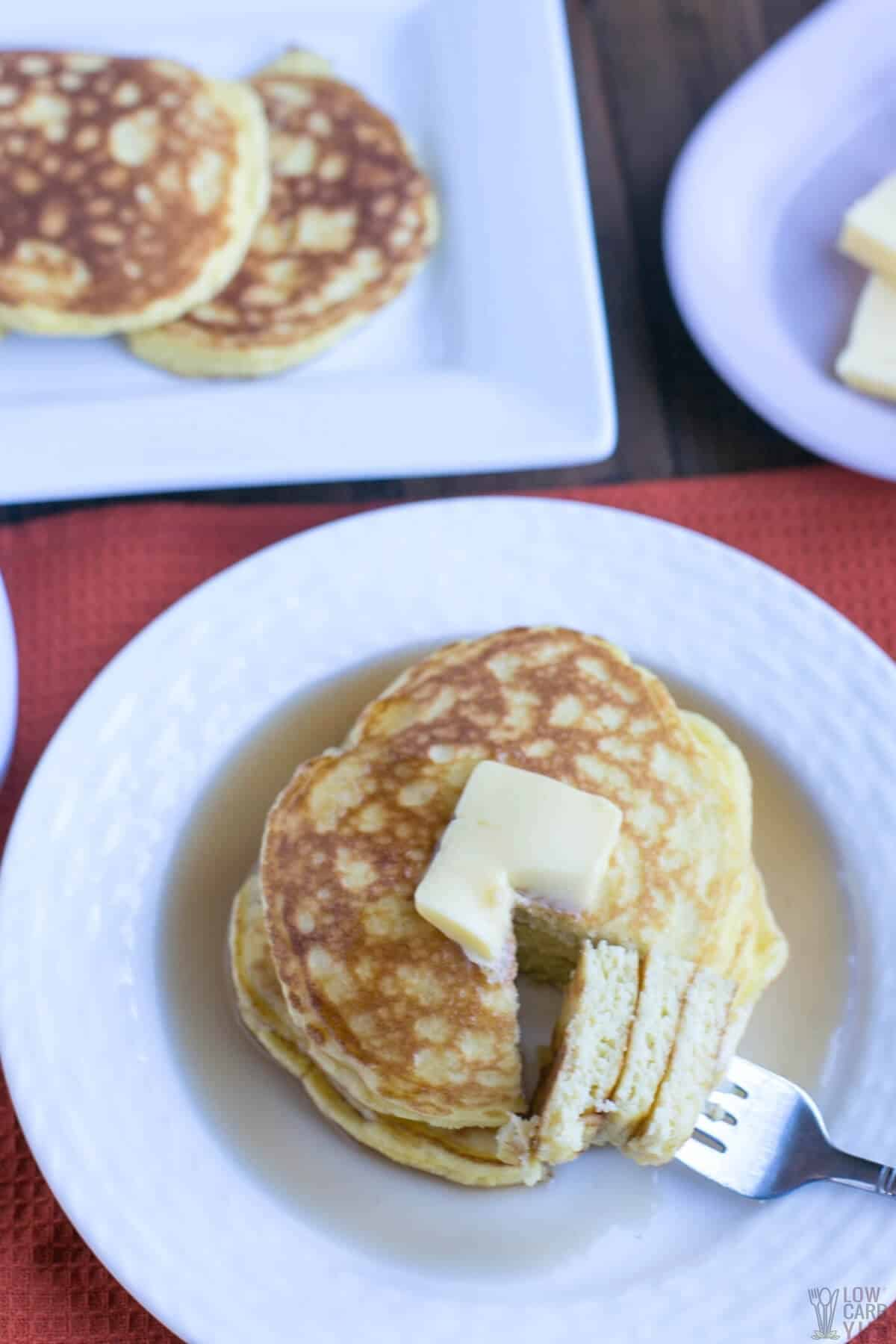 keto coconut flour pancakes on white plate with fork bite