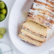 sliced key lime bread on platter with limes