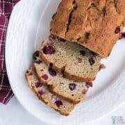 loaf of cranberry bread sliced on platter