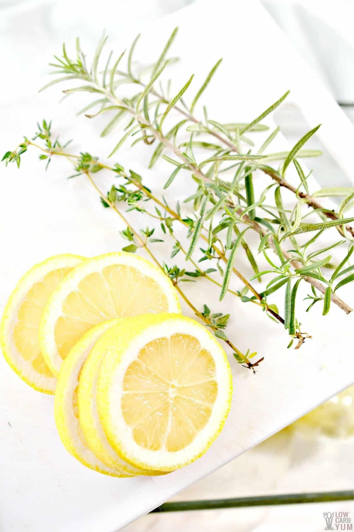 sliced lemon, rosemary, and thyme spigs on plate