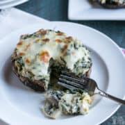 spinach stuffed portobello mushroom on plate with fork bite square image