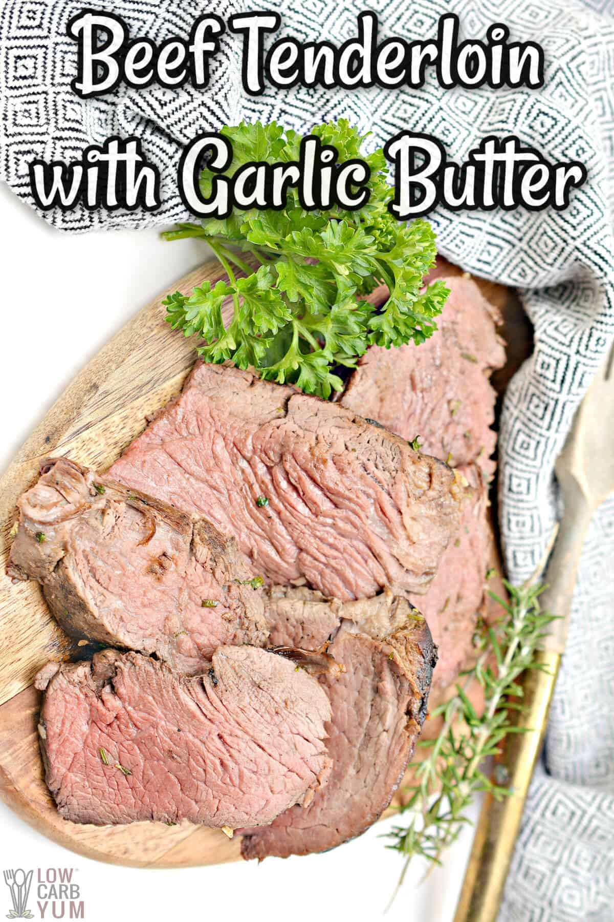 beef tenderloin with herbed garlic butter sliced on cutting board