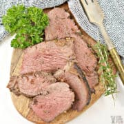 garlic butter beef tenderloin slices on wood cutting board