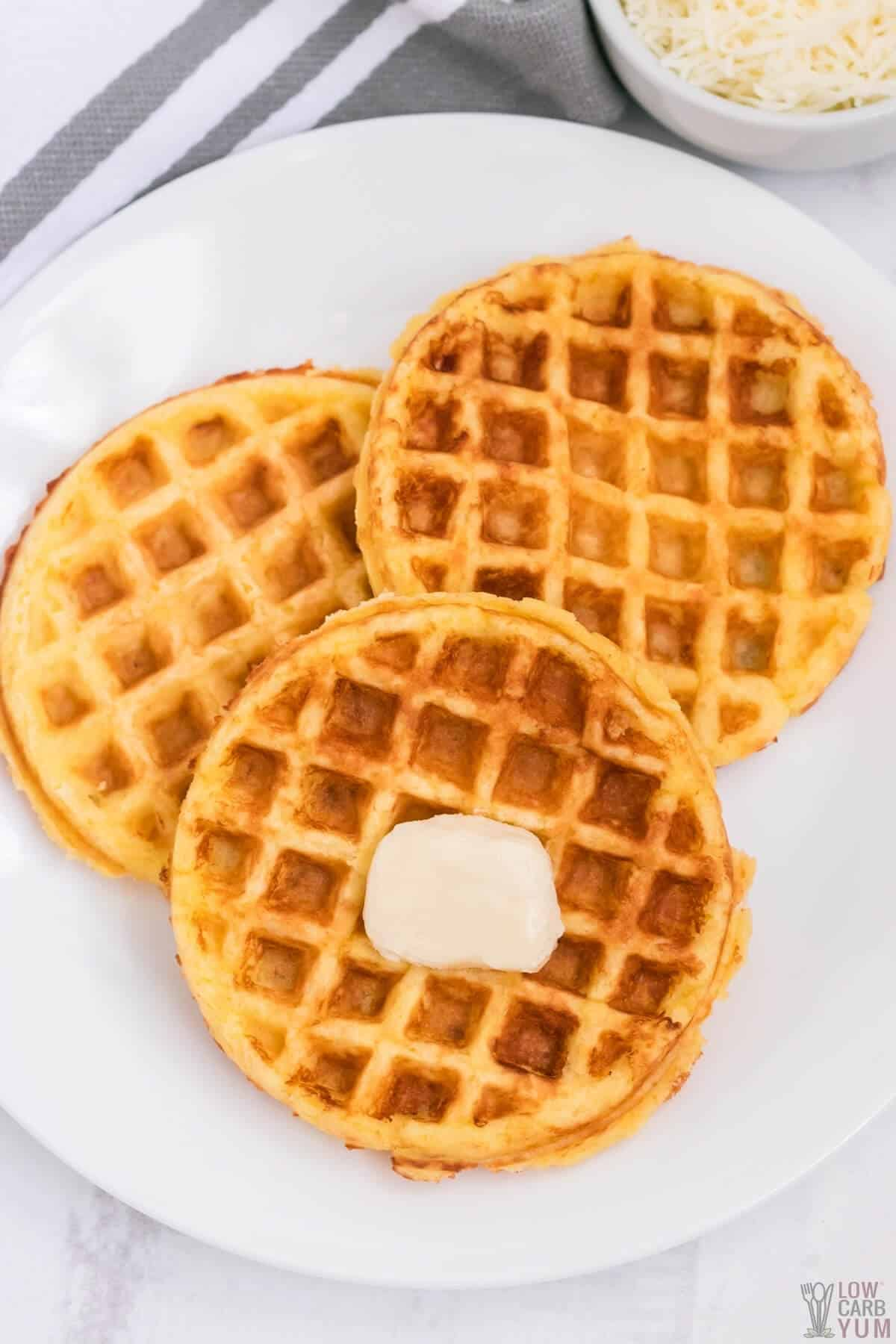 three chaffles on white plate with pat of butter