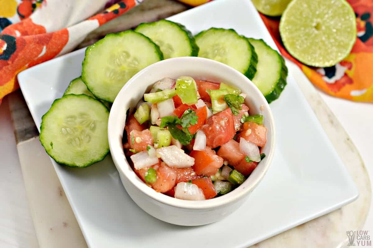fresh salsa in small bowl with cucumber slices