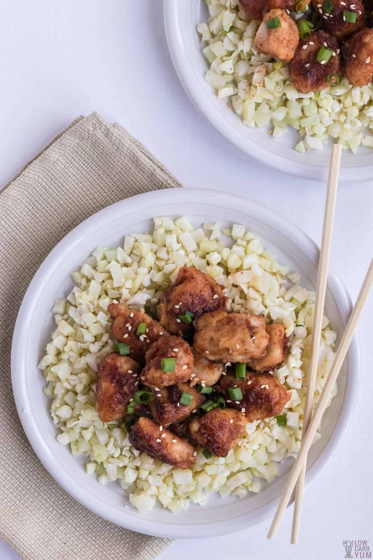 overhead of keto sweet and sour chicken over cauliflower rice on plates