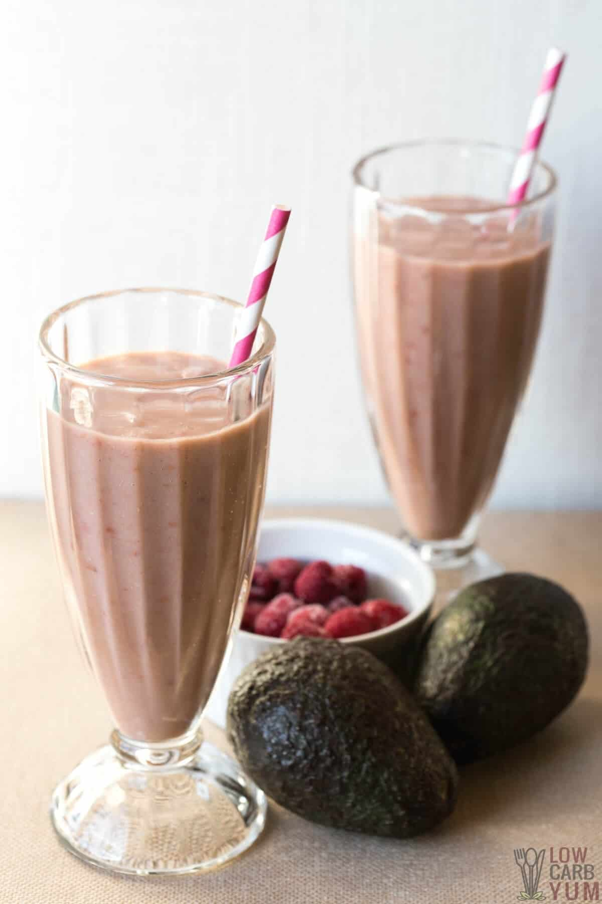 keto raspberry avocado smoothies in glasses with frozen berries and avocados