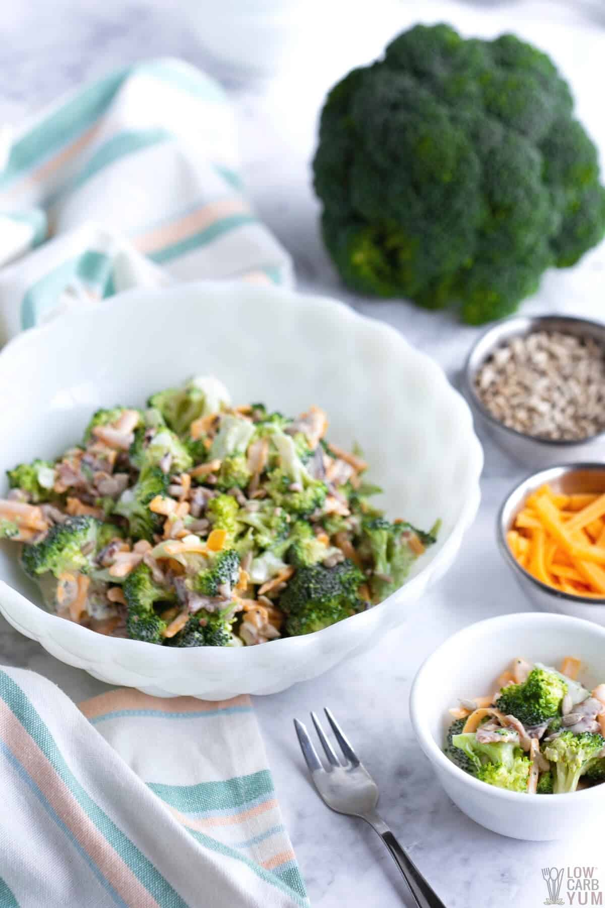 broccoli salad in white bowl with toppings on the side