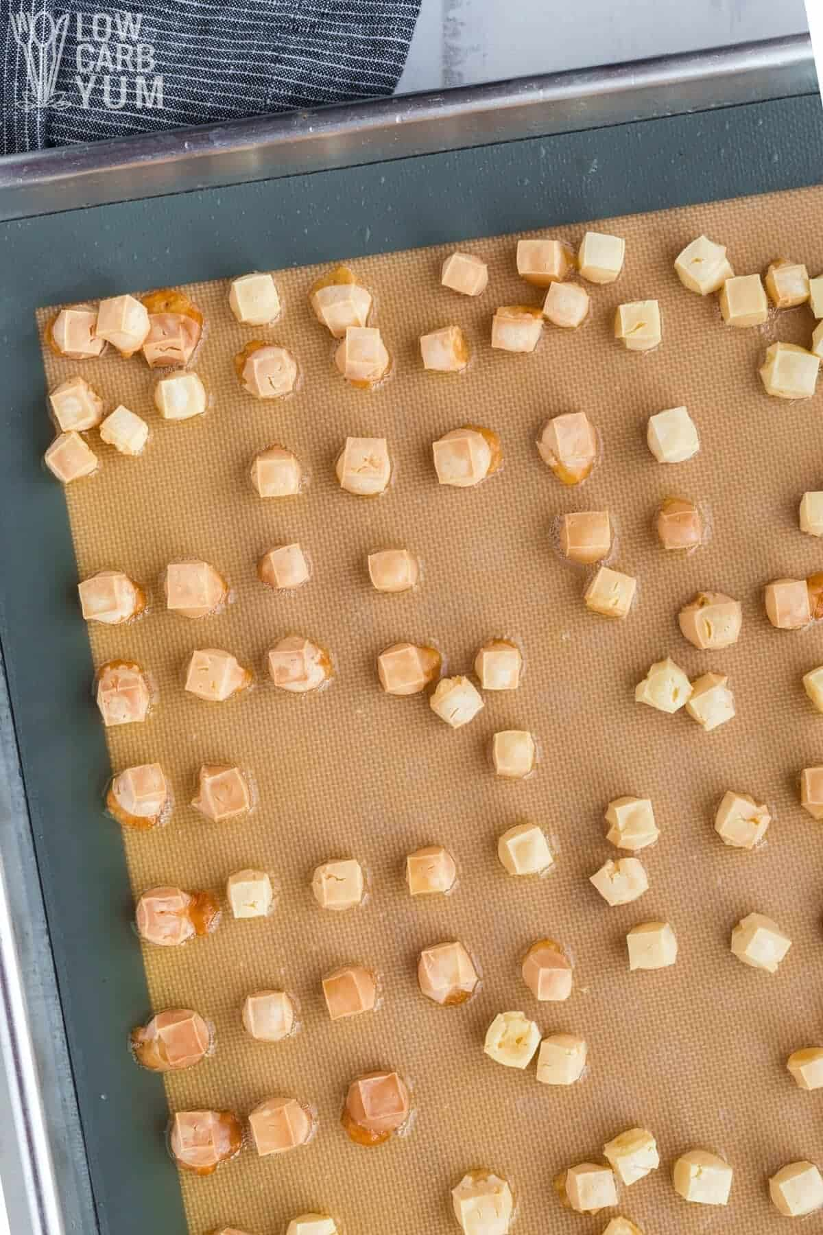 baked cheese cubes after baking on lined sheet pan