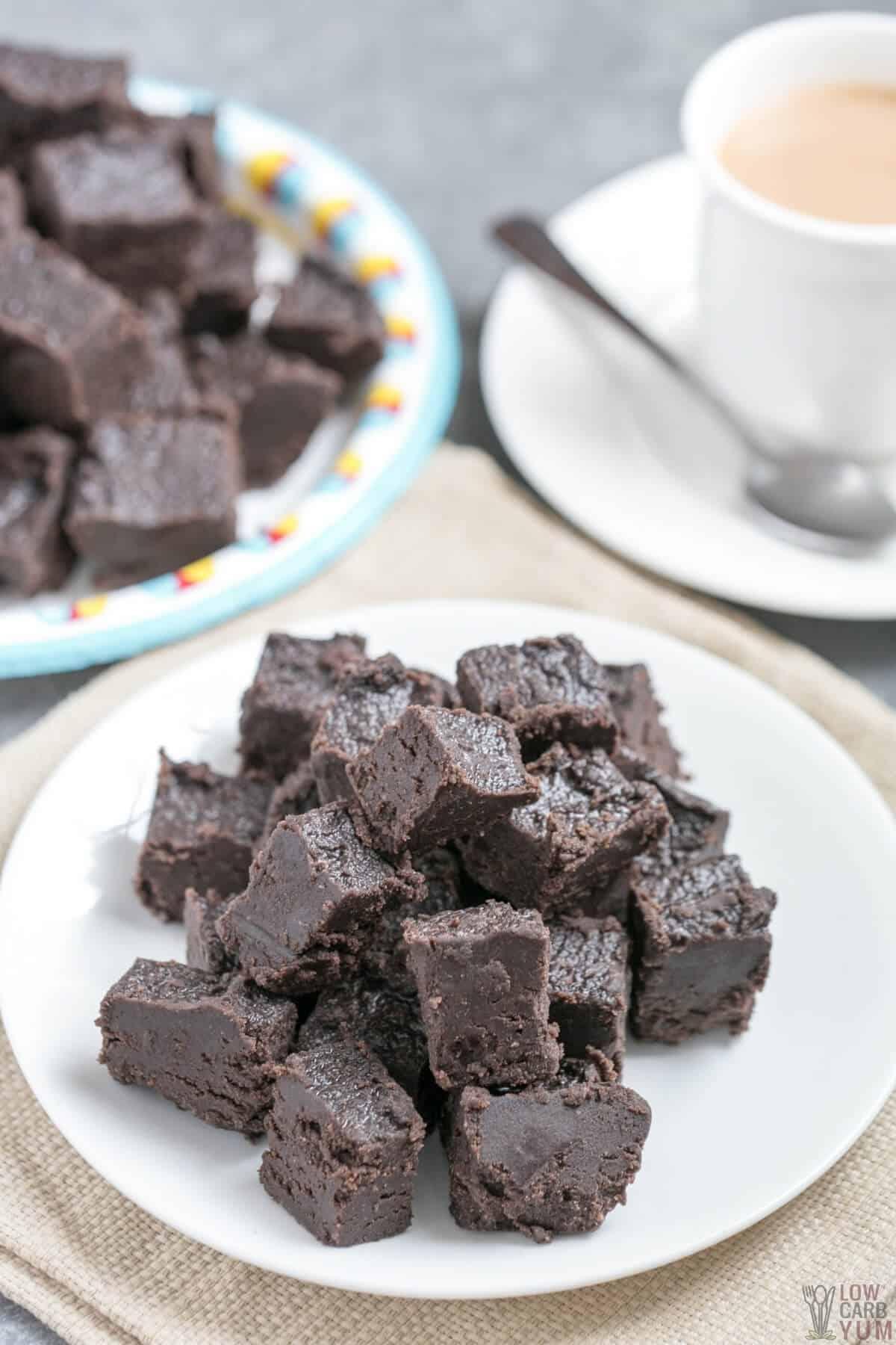dark chocolate keto fudge squares on plates with coffee
