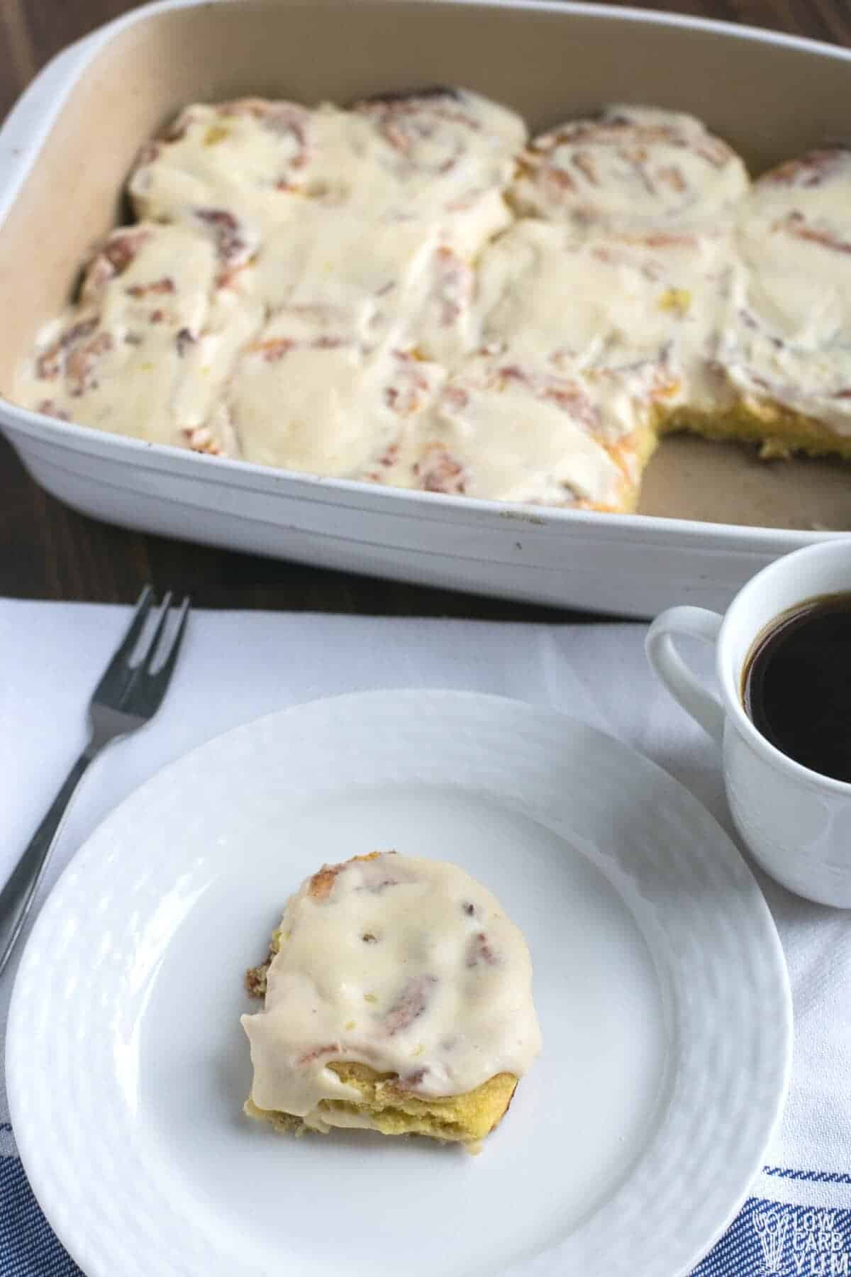 cinnamon rolls in casserole pan and on white plate with coffee
