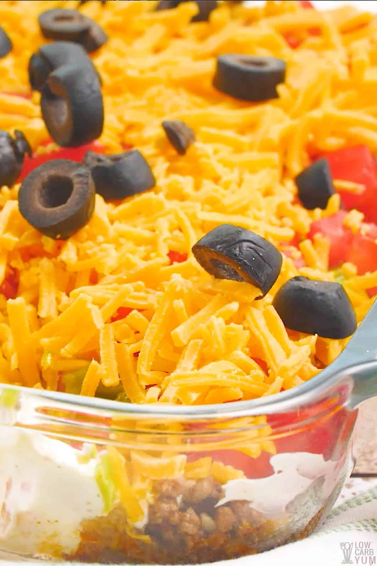 layered keto taco dip with meat in casserole pan
