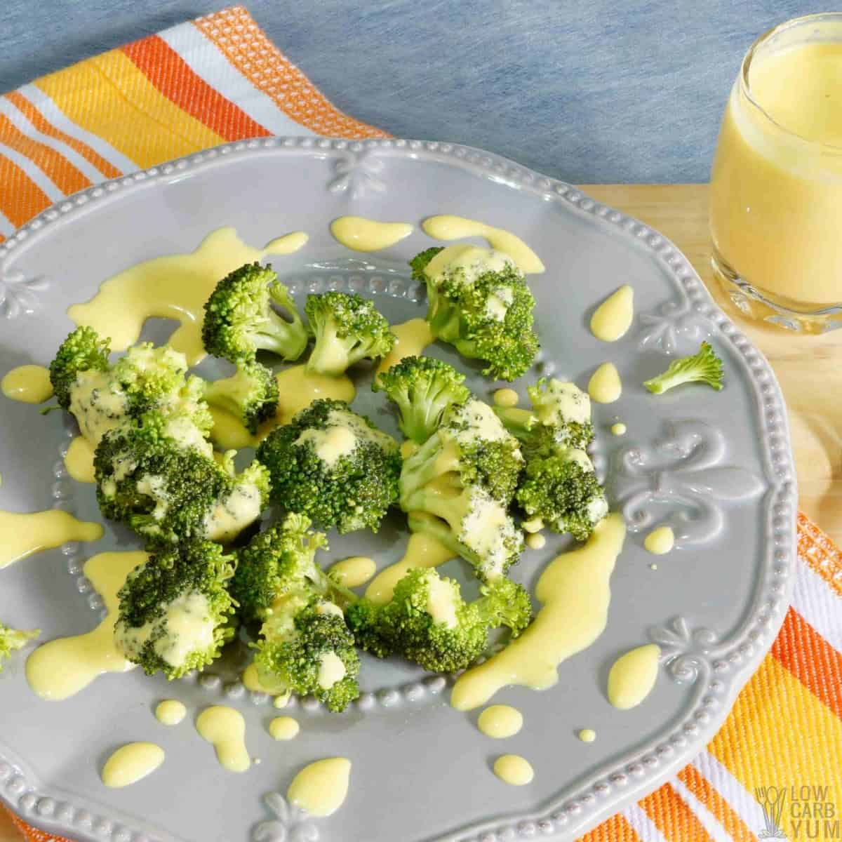cheese sauce drizzled over broccoli on plate