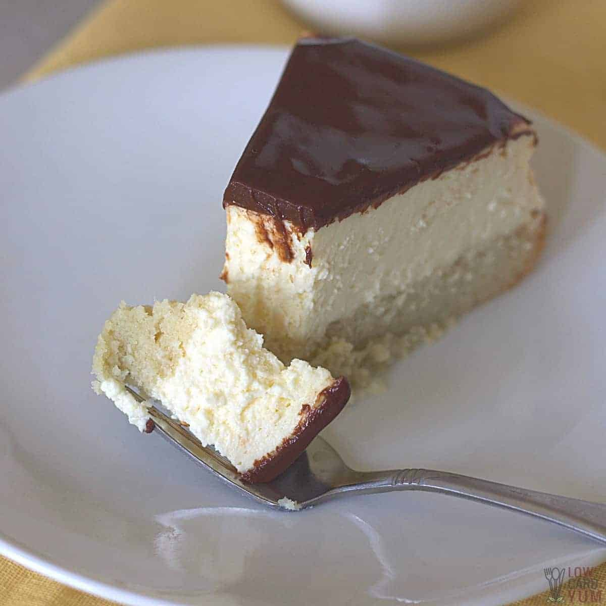 cheesecake slice with fork bite on plate