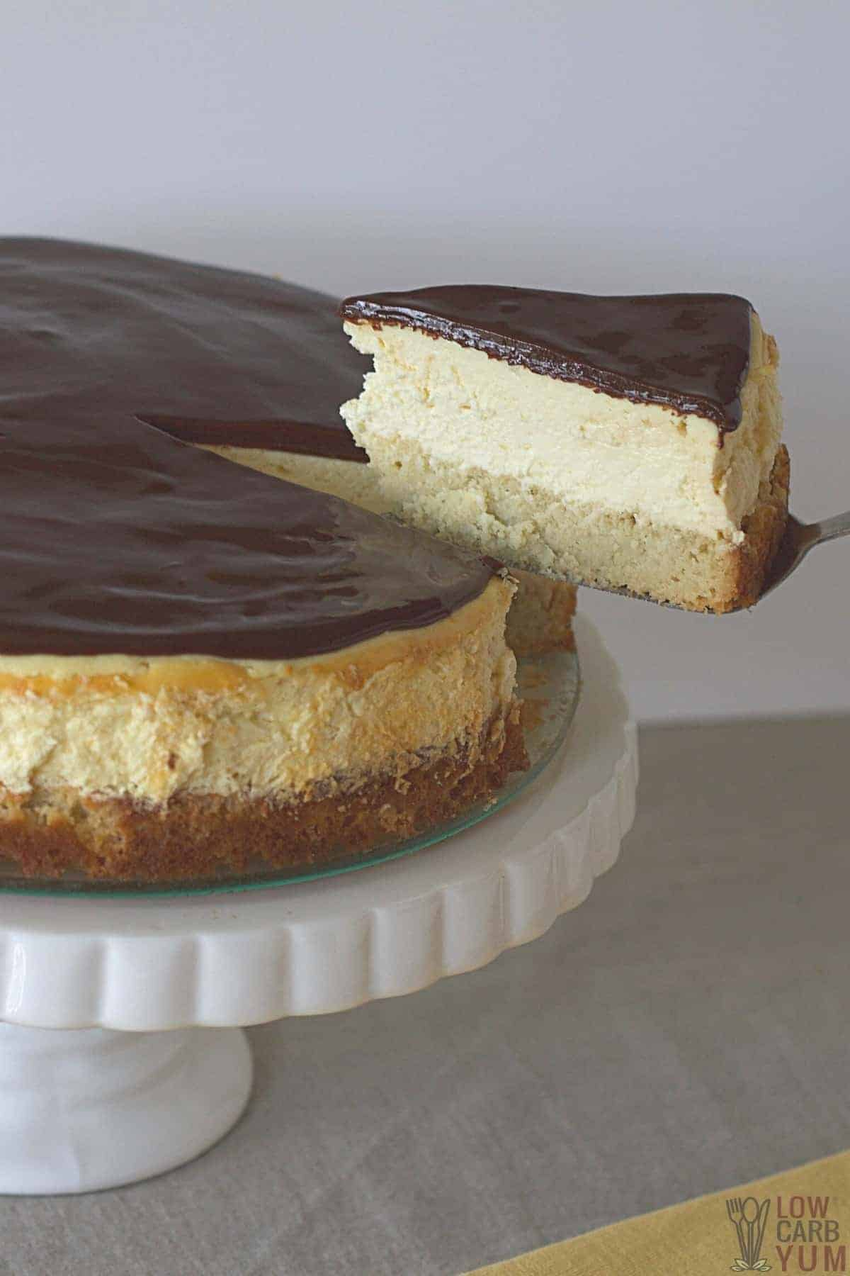 tall image of slicing the boston cream pie cheesecake on cake plate
