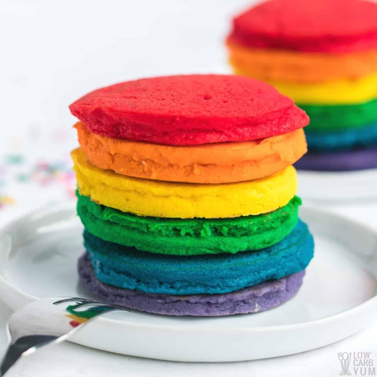 stacks of rainbow pancakes on white plates