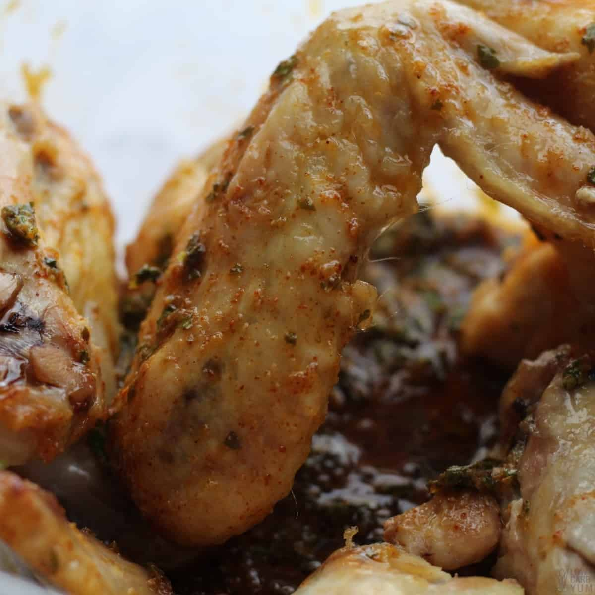 combining sauce with wings in bowl