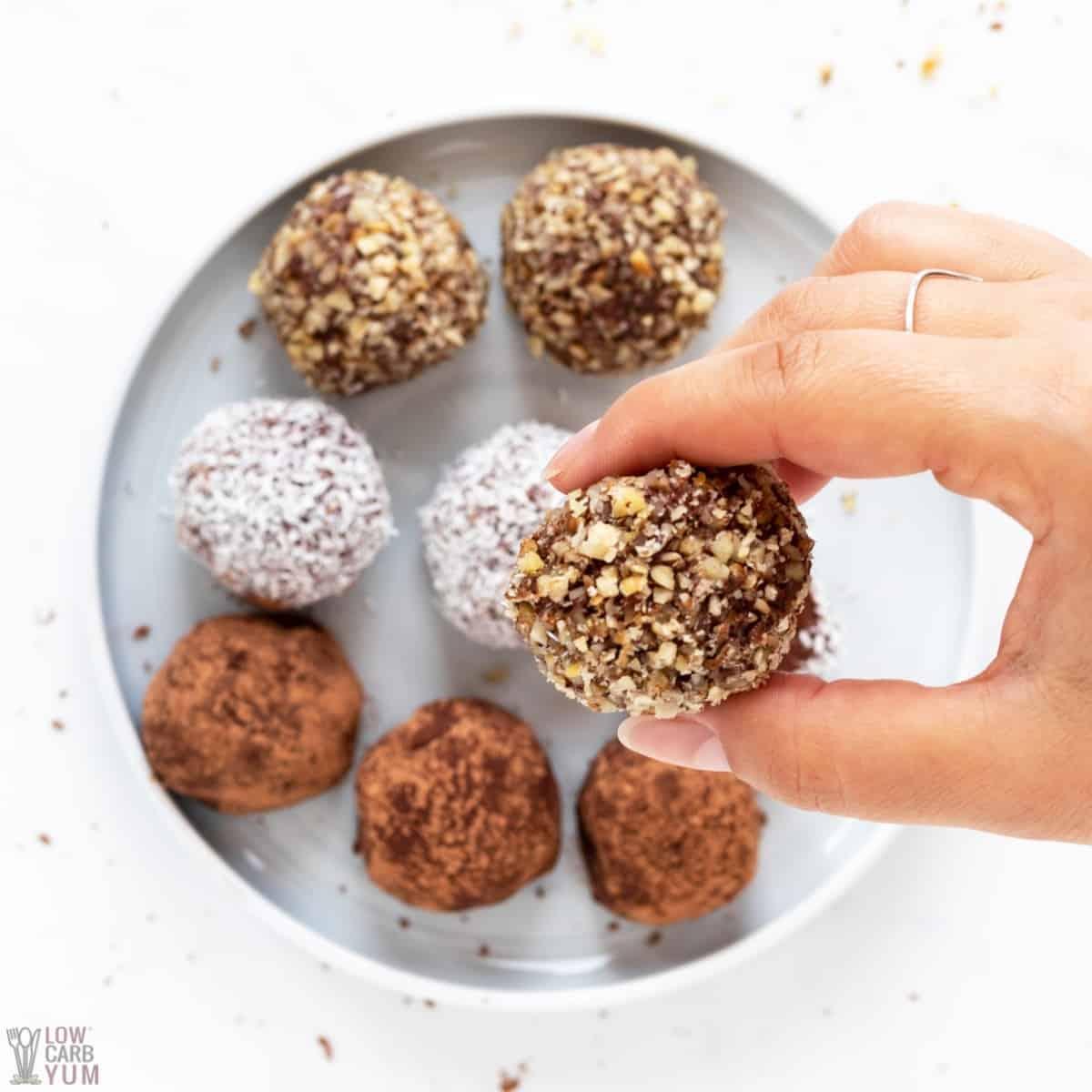 hand picking up nut covered chocolate cream cheese ball truffle