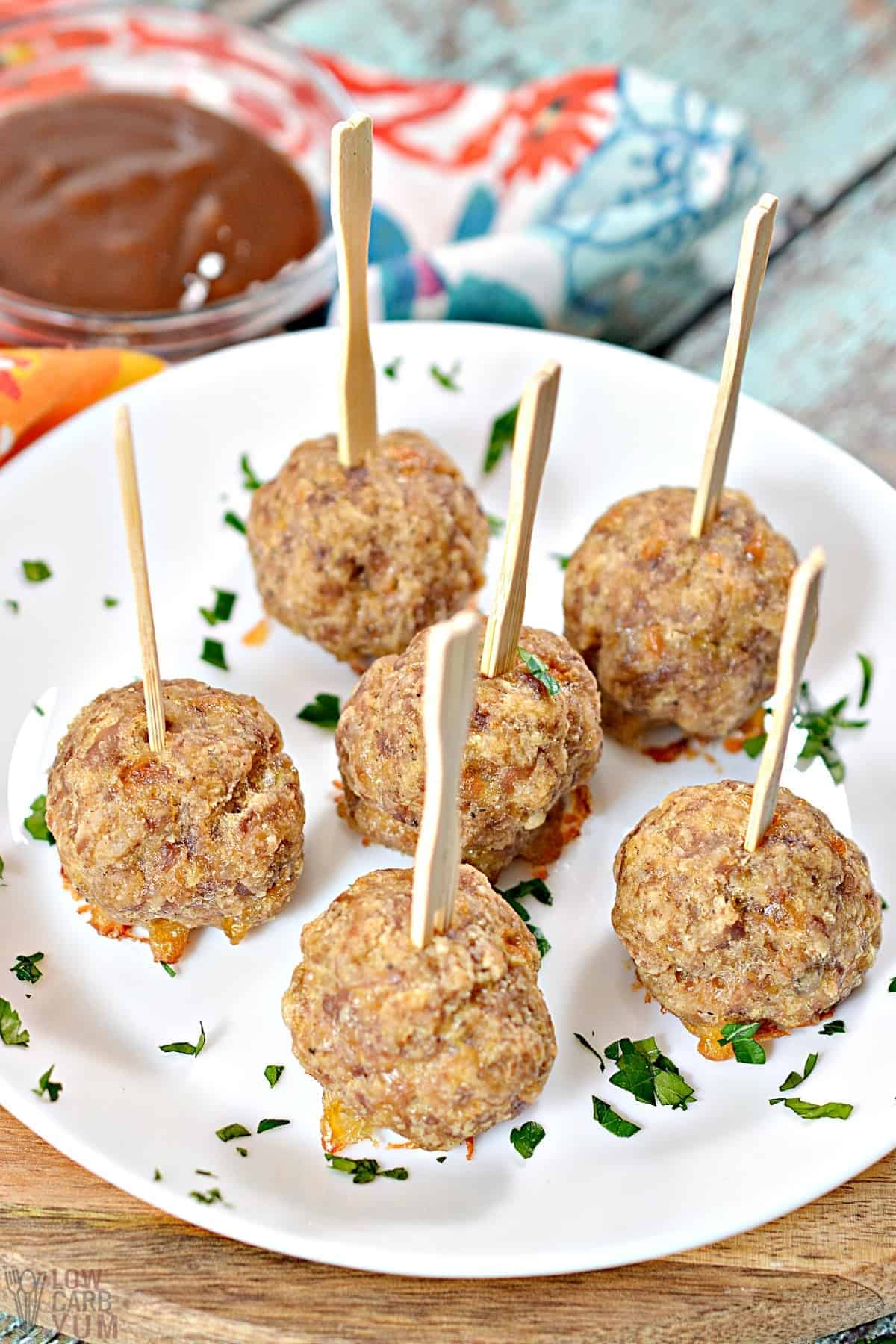 sausage balls with sticks on white plate with dipping sauce