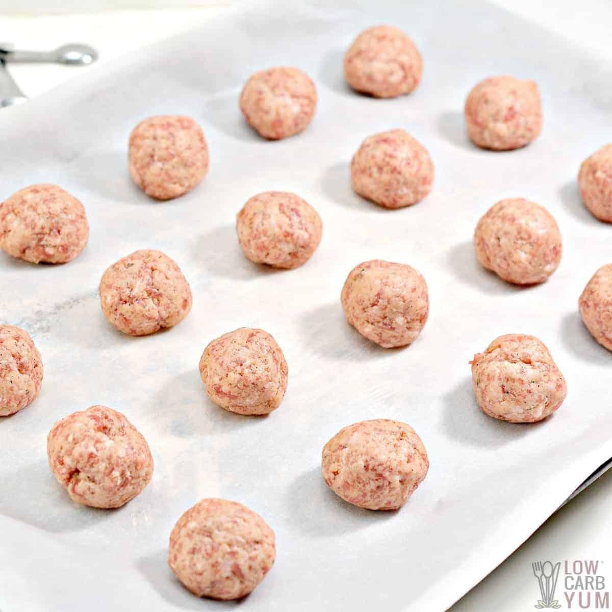 raw sausage balls on lined baking sheet
