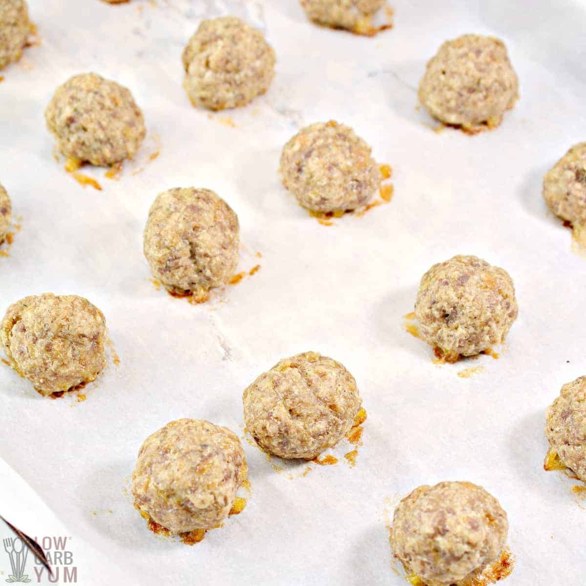 cooked sausage balls on lined baking sheet