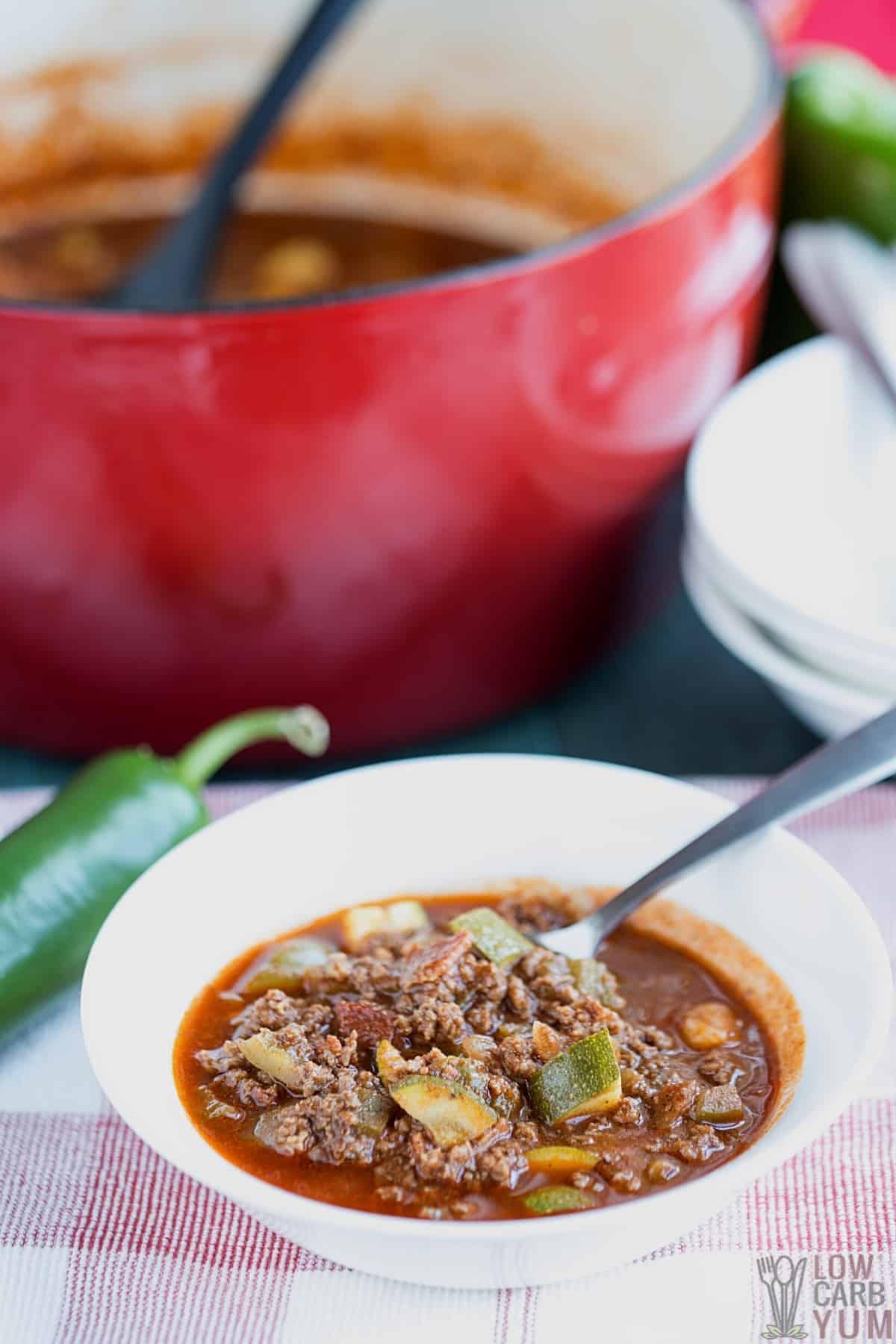 serving venison chili in white bowl