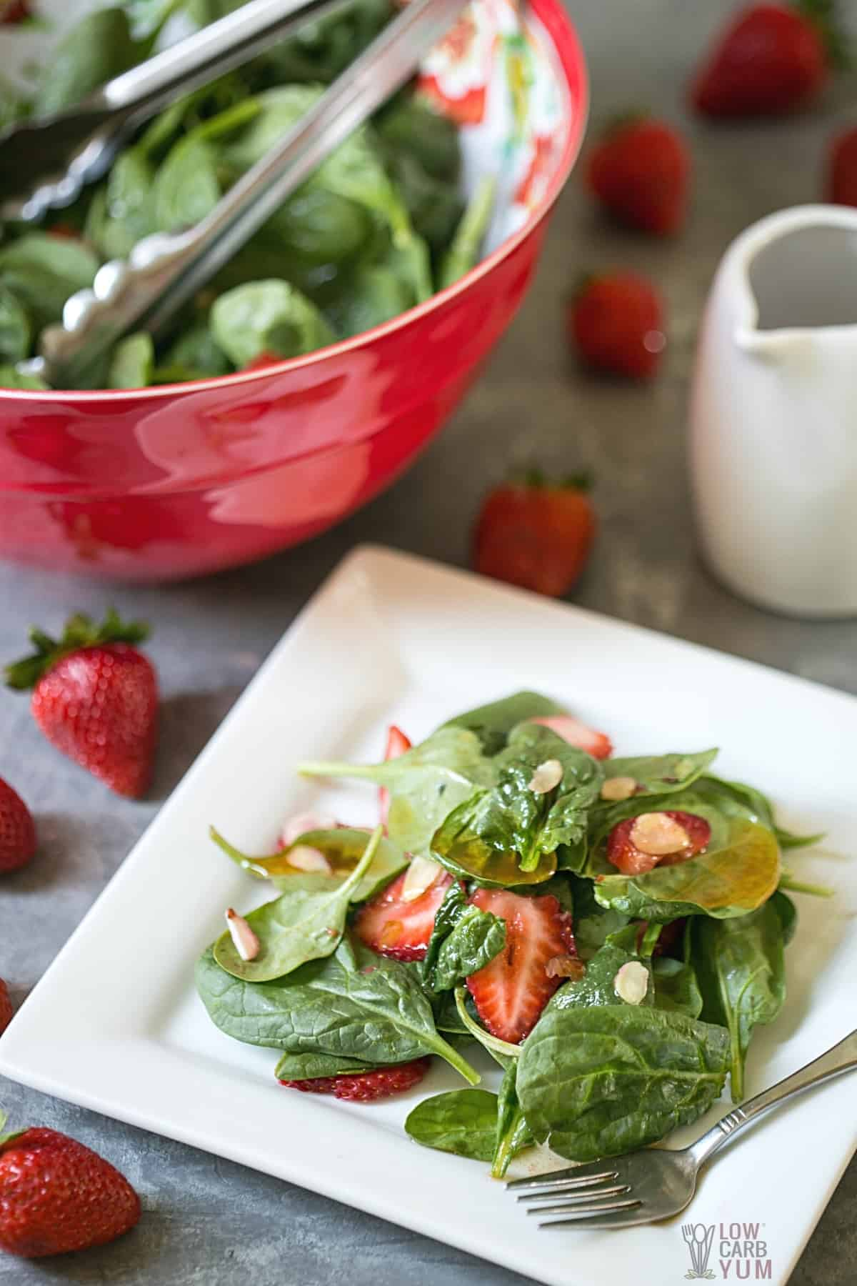strawberry spinach salad on white square plate with vinaigrette dressing