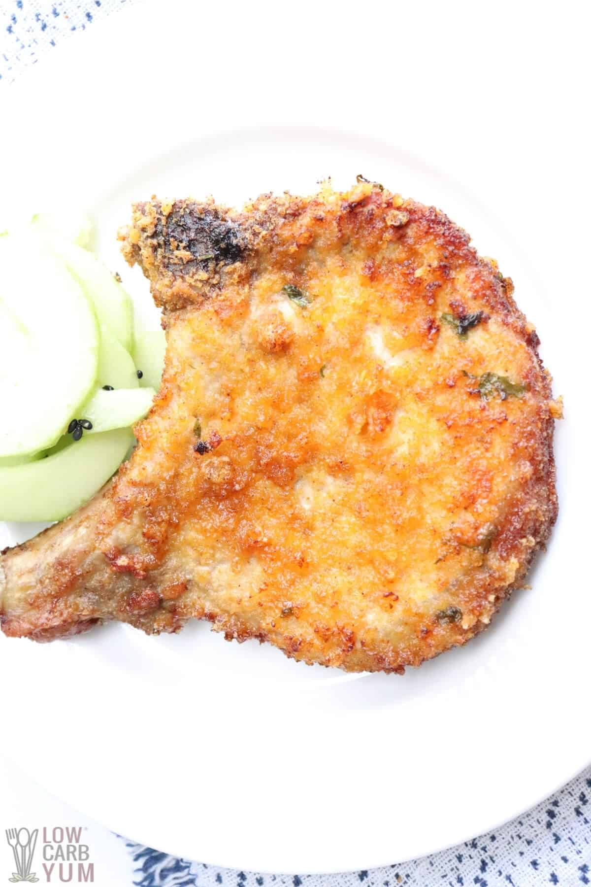 keto air fryer pork chop on white plate with cucumber salad