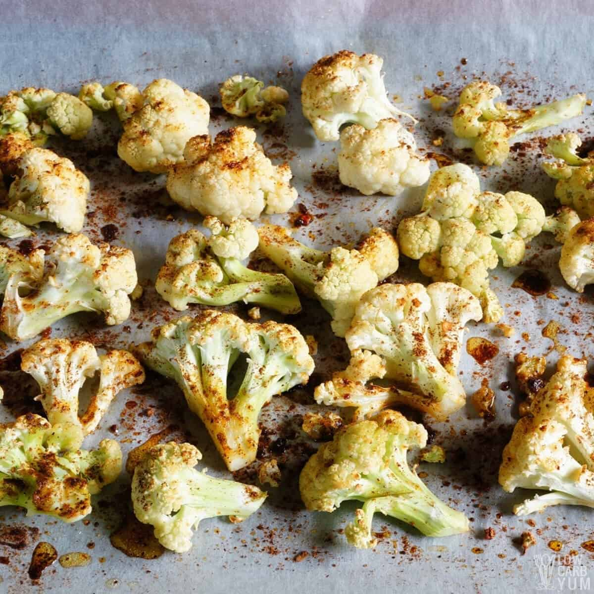 roasting seasoned cauliflower on lined baking sheet