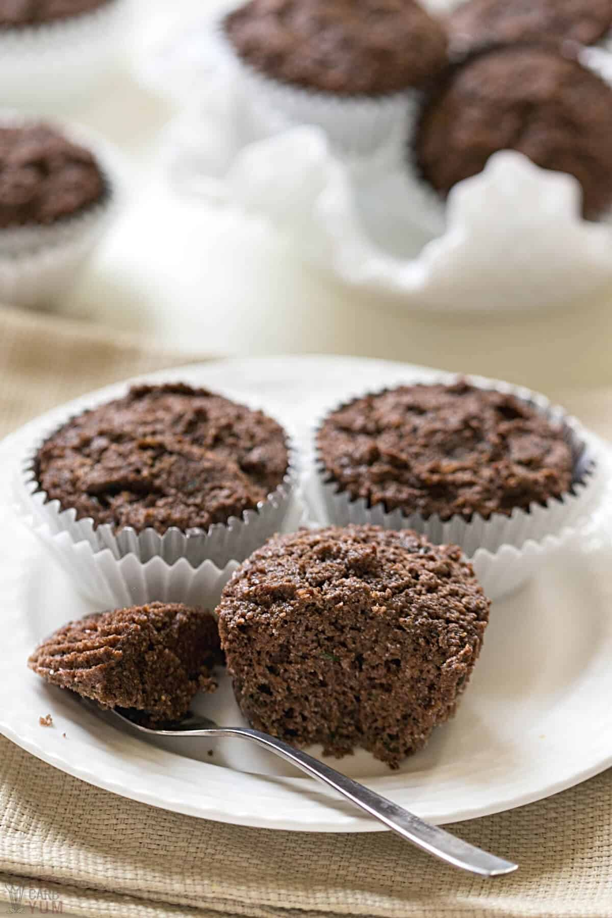 chocolate zucchini muffins with one cut on plate