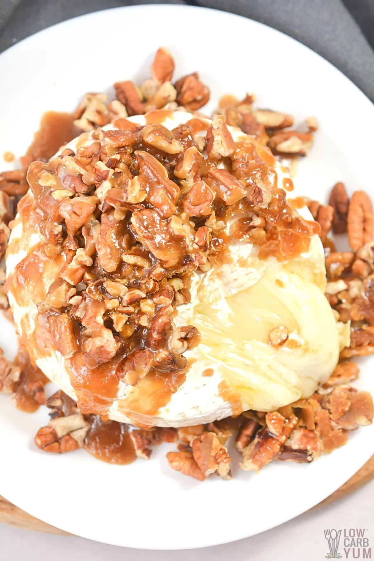 pecan baked brie on plate with cheese oozing out