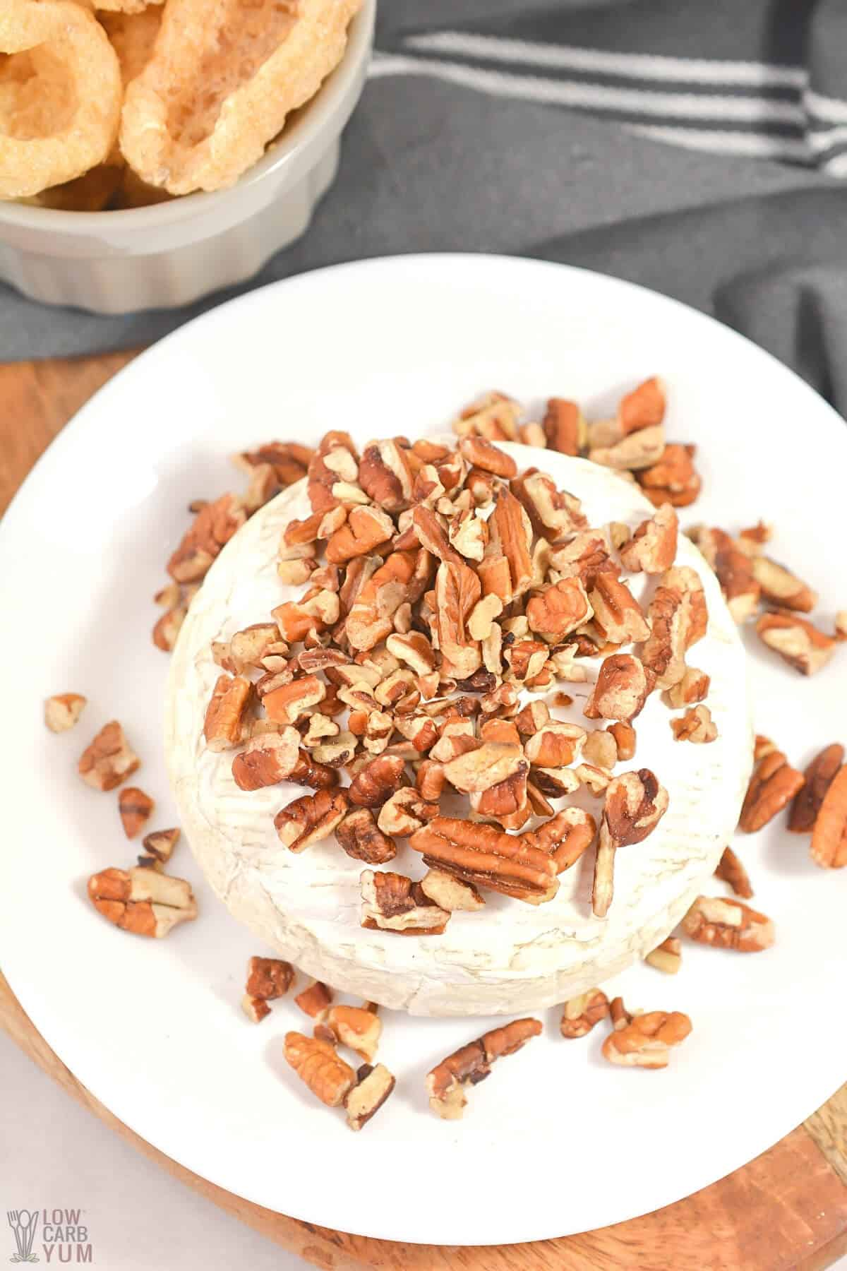 pecan topped baked brie on white plate